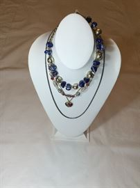 Four costume jewelry necklaces.