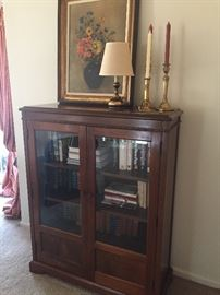 Bookcase with glass doors - bottom shelf hidden by lower panels, brass candlesticks and lamp and acrylic framed picture
