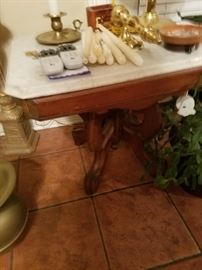 Marble top table. Lots of candles, brass, and crystal candlesticks.