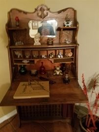 Very, very old secretary and many old trinkets shown on it. Set of old  encyclopedias on the bottom.