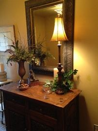The large mirror, stunning antique chest, and other accents will welcome you in the entry.