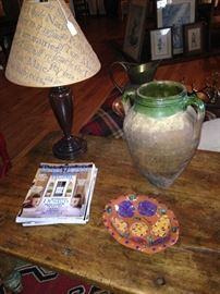 Table lamp, colorful bowl, and primitive jug on antique table