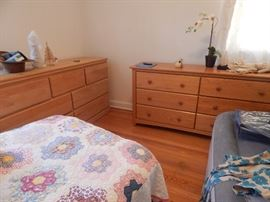 Mid century bedroom light oak bedroom dressers, twin bed, quilts and a blow up stow away bed.