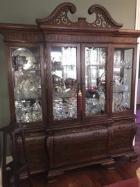 huge china cabinet filled to the top with crystal, china, and silver