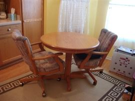Small wood pedestal table with 2 upholstered swivel chairs