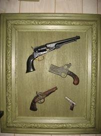 Mounted replica antique pistols.