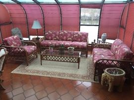 The beautiful solarium has a lovely set of rattan furniture.
