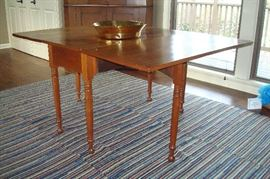 1840's antique walnut gate leg table and one of two hand made  btaided rugs.