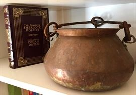 Vintage copper pots, collection of leather-bound classic book titles.