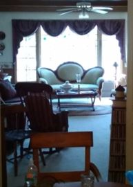 View of TV room with antique and newer furniture, stereo equipment, tables and more