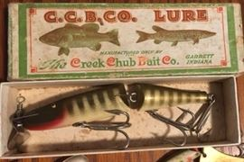One of twenty vintage lures, most not in boxes. tackle boxes, two fishing poles and four reels