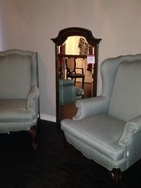 Matching upholstered wingback chairs; tall wall mirror