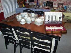 DINING TABLE (HAS LEAF), 6 BLACK PAINTED CHAIRS, NORITAKE DINNER SET & PLATED FLATWARE SET