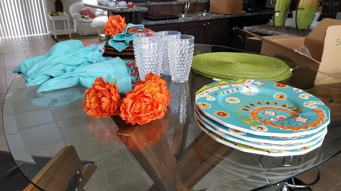 4 piece place setting of Pier One: floral dishes, napkins, placemats, flower napkin rings, and plastic glasses,