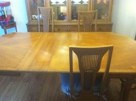DINING ROOM TABLE HAS ALWAYS BEEN COVERED HAS 2 LEAVES IN IT AND ANOTHER ONE THAT CAN BE PUT IN IT