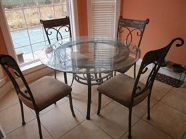 Metal and glass table  Chairs have stained glass motif.