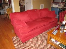 Matching sofa and love seat.  Red fabric.  Note the area rug.