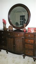 Double dresser and round mirror matching master bedroom furniture