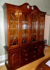 "Thomasville china cabinet (top and bottom separate for moving).  Glass doors with fretwork, glass shelves with plate grooves, lighted, bottom storage of three  drawers and side storage areas.  68"" x 18"" x 84"" tall."