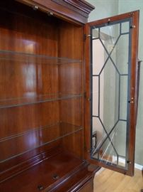 """Thomasville china cabinet (top and bottom separate for moving).  Glass doors with fretwork, glass shelves with plate grooves, lighted, bottom storage of three  drawers and side storage areas.  68"""" x 18"""" x 84"""" tall."""