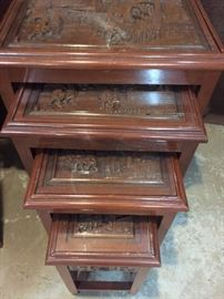 Asian nesting tables (4) with intricate carved details.