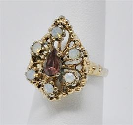 Costume ring with purple center stone, and six opal-like stones surrounding it. Gold plated.