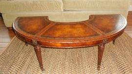 "Living Room:  The classic  vintage mahogany/leather top hunt-style coffee table has six legs and measures 48"" wide.  There is a drop leaf at each end which can be raised by rotating the leg to support the leaf."