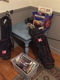 Kids' golf clubs, hockey memorabilia, Baseball memorabilia, blue table, rug