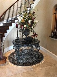 Gorgeous wrought iron and marble table with large floral arrangement and decor and round rug
