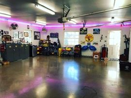 Harley Davidson garage cabinets - vintage motorcycle and antique car art, neon, tools - Vintage Lube Machine, Vintage Harley Doormat, small refridgerator, loads of car and motorcycle products,  rolling carts. The blue Indian parts have sold and the jaguar neon