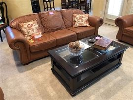 Leather sofa with nailhead trim and lovely black coffee table  with glass inserts and 2 drawers with shelf