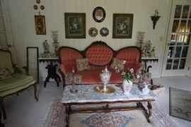 Marble top coffee table, pictures, rug, green arm side chair, and victorian sofa.