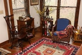 Comfortable wicker chair next to a revolving bookcase.
