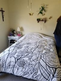 Full size bed and comforter, wicker nightstand and wall decor