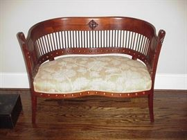 Sweet upholstered loveseat with curved, spindle back, 19th century