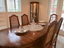 Vintage oval dining table with 3 leaves and 6 chairs. Lighted curio cabinet in far corner.