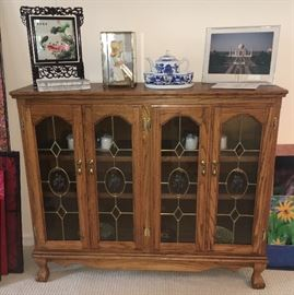 Low oak china cupboard with leaded glass doors, Chinese screen decor, blue and white tea set and photo print of Taj Mahal.