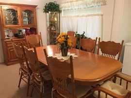 Oak dining table with a leaf and 8 chairs.  Makes a real family-sized table.  Matching china hutch.