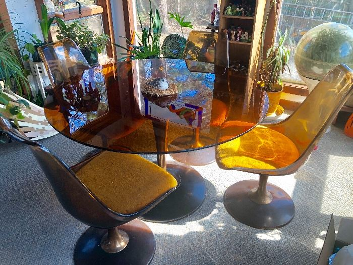 Chromcast Mid-century and in nice condition. Amber smoked glass top and smoked lucite chairs with heavy tulip base.