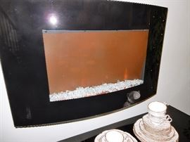 Wall mounted electric fireplace with glass crystals.