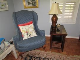 Blue, newly upholstered spoon foot wing chair, Mahogany side table with lower basket, decor lamp, pillow decor