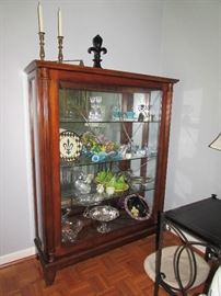 Henredon sliding front Mahogany display cabinet wiht glass shelves.  Brass candle sticks by Virginia Metal Crafters and others.  Silver and silverplate items.
