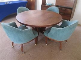 "MCM Dining/Game Table with pedestal legs.  4-Barrel Chairs on casters and 2-24"" leaves.  Table size: 48"" Diameter.  Overall size with both leaves 96"" X 48"""