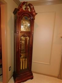 Howard Miller Grandfather Clock  86 inches Landsbury This floor clock features an elegant, swan neck pediment with an overlay of crotch mahogany crowned with an applied shell.