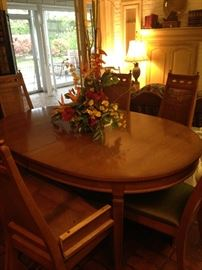 Oval dining table has 8 chairs and several leaves.