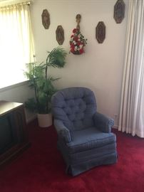 Swivel chair and wall art and plastic plant