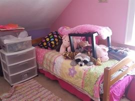 Twin bed with girl's bedding and stuffed animals, small end table and plastic storage bins