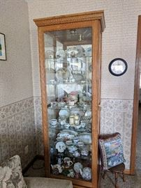 Tall, lighted curio cabinet with sliding front door