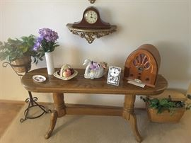 Front Entry Maple Table with Vintage Radio Look a like, Wall Clock, Wrought Iron Plant Stand, Collectible Vases, Fruit Basket, Mini Table Clock, Ring Tray Made in England, and Swan Collectible. Woven Basket for Picnic with Ivy.