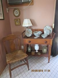 Pine wash stand has oil lamp on top and oriental dishes. The tiger maple rush seat chair.